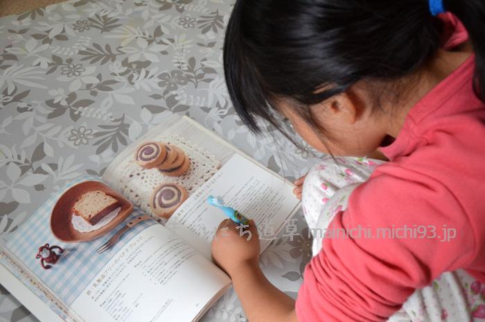 朝のハミガキをしながら、レシピ本を見る長女